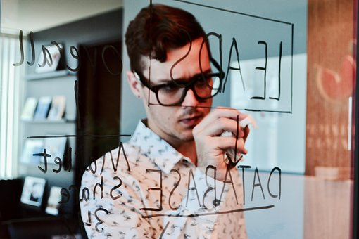 guy writing leads on glass wall
